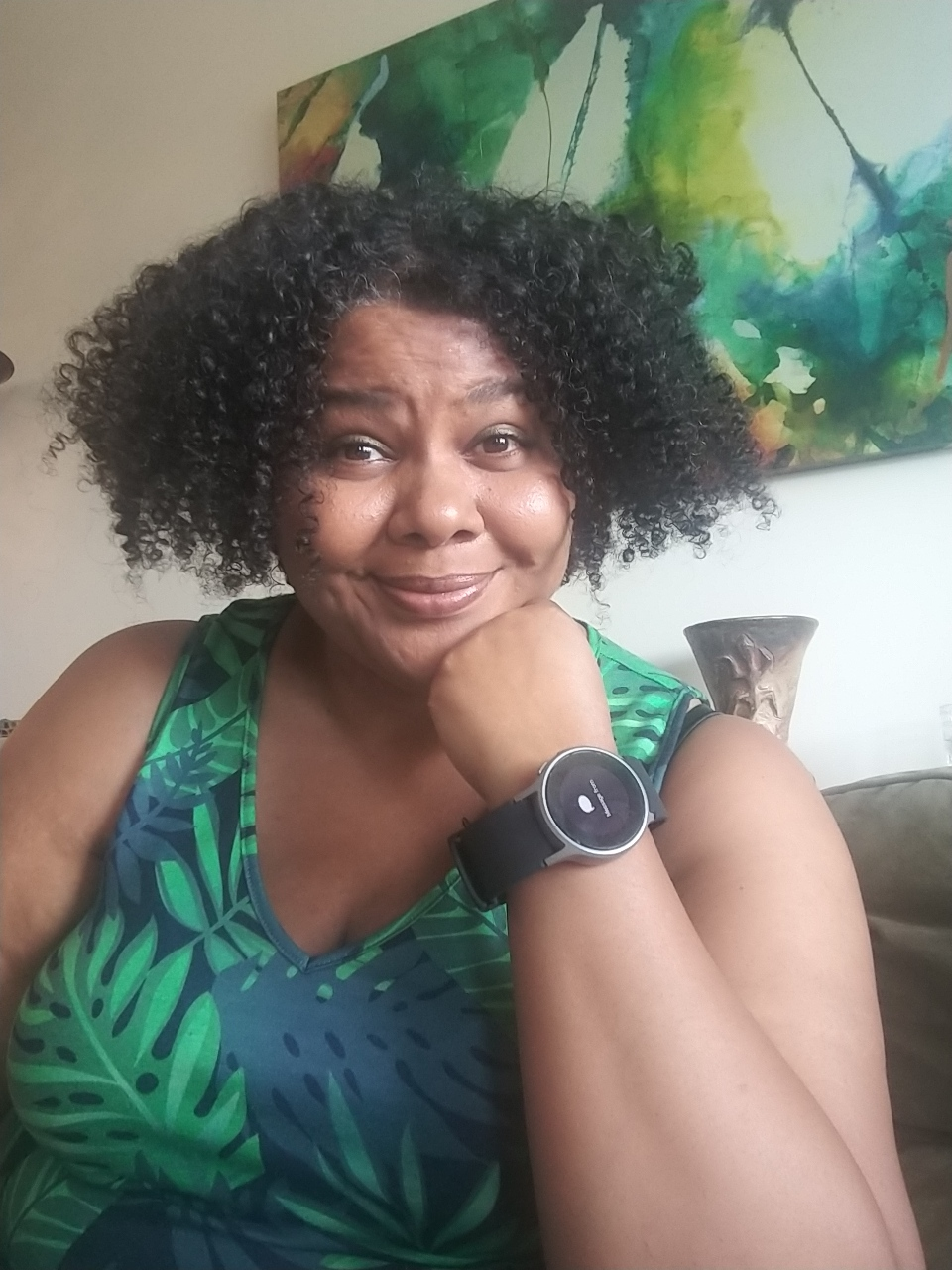 A Black woman with natural hair wearing a blood pressure smart watch